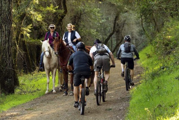Mountain bikers pass horseback riders Tammi Bernd, left, and Colleen Simmons, on the Warren Richardson trail in Annadel State Park. (John Burgess/ The Press Democrat)
